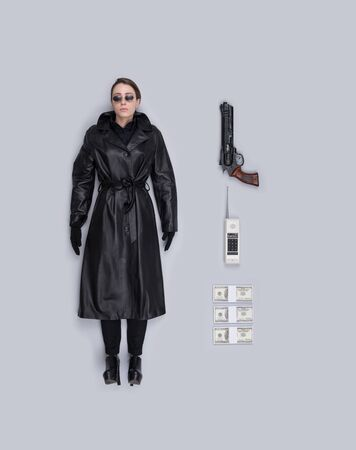 Lifelike female spy agent human doll with leather coat, gun and accessories, flat lay