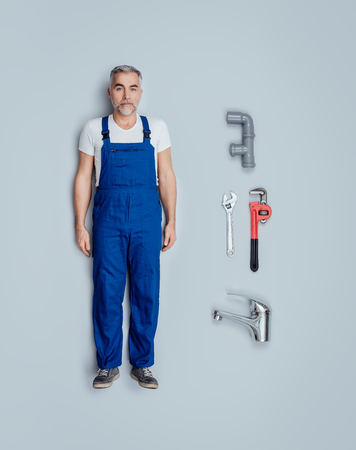 Realistic plumber toy doll with plumbing and house repair tools, flat lay