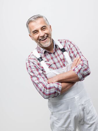 Confident smiling painter with white overalls posing with arms crossed