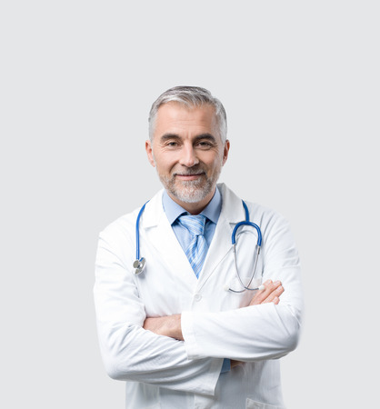 Confident mature doctor posing with arms crossed, he is smiling at camera