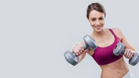 Smiling young sportswoman working out with dumbbells, sports and training concept