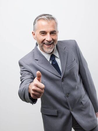 Confident corporate business executive giving a thumbs up and smiling at camera