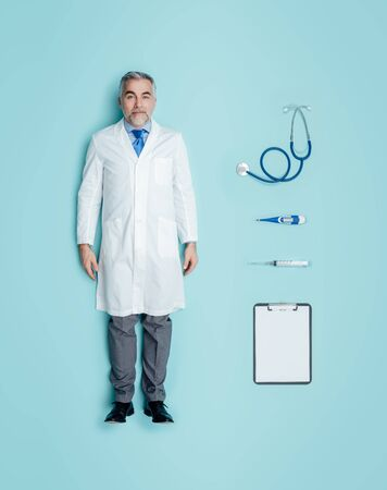 Lifelike male doctor human doll wearing a lab coat and medical equipment accessories, flat lay