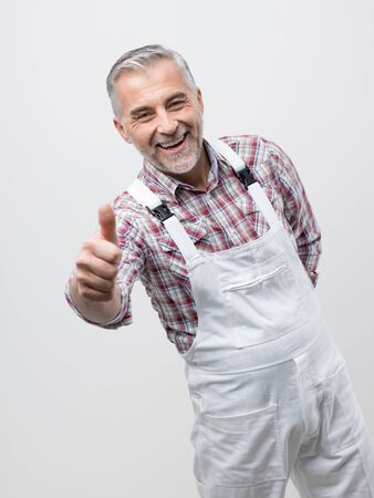 Smiling professional painter in dungarees giving a thumbs up