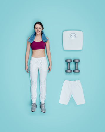 Lifelike sportswoman smiling human doll with sportswear clothing and sports equipment, flat lay
