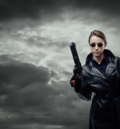 Cool female spy agent in black leather coat, she is holding a gun and posing Stock Photo