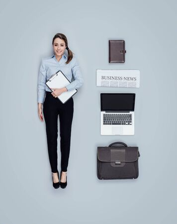 Realistic businesswoman smiling human doll with accessories, flat lay
