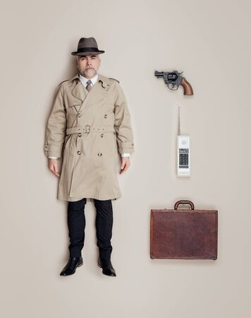 Vintage spy agent lifelike doll wearing a trench coat and a hat, flat lay accessories