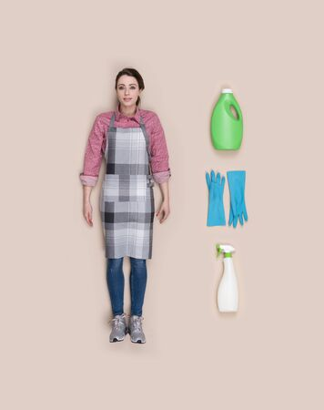 Lifelike smiling housewife human doll with apron and housekeeping objects, flat lay