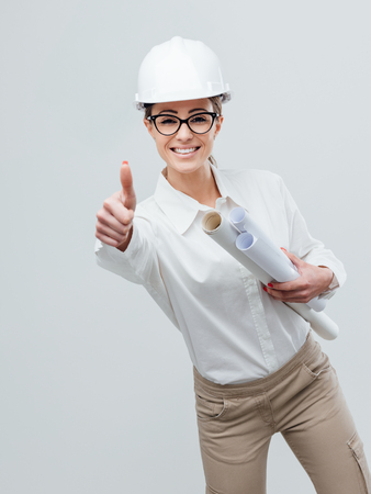 Cheerful female architect and construction engineer giving a thumbs up and holding project paper rolls