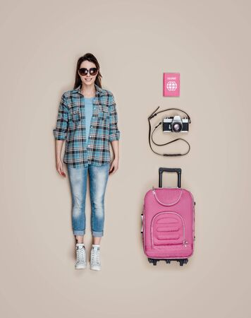 Lifelike smiling tourist female human doll with accessories: camera, trolley case and passport, flat lay