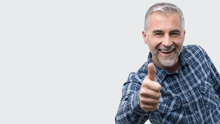 Cheerful mature man smiling and giving a thumbs up