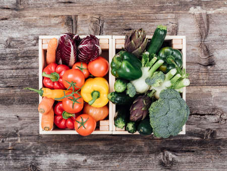 Fresh tasty colorful vegetables in wooden crates on a rustic wooden table