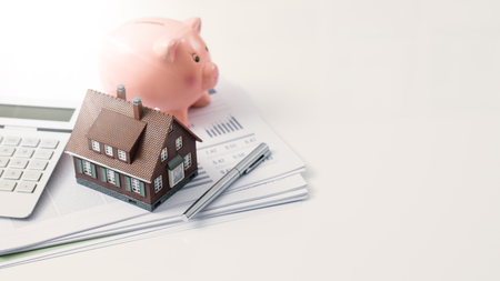 Model house, piggy bank, calculator and financial report on a desk: real estate, investments and home loan concept Stock Photo