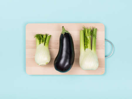 Fresh fennels and eggplant on a wooden chopping board, food preparation and healthy eating concept