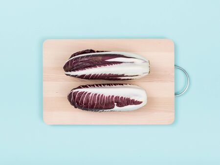 Fresh red chicory heads on a wooden chopping board, food preparation and healthy eating concept