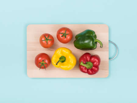 Fresh peppers and tomatoes on a wooden chopping board, food preparation and healthy eating concept Stock Photo