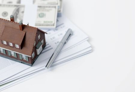 Model house, calculator, cash money and paperwork on a desk: real estate, home loan and investments concept Stock Photo