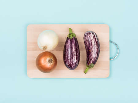 Onions and eggplants on a wooden chopping board, food preparation and healthy eating concept Stock Photo