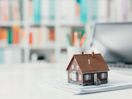 Model house and paperwork on a desktop: real estate, investments and home loan concept