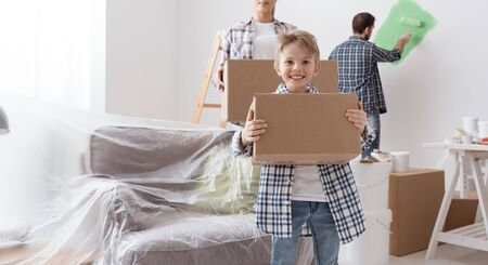 Happy family moving in a new house: they are carrying boxes and painting rooms, boy smiling on the foreground Imagens