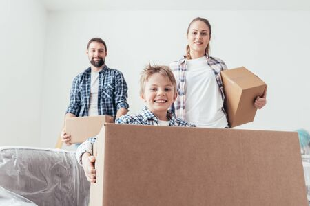 Young family relocating and renovating their new house, they are carrying boxes, boy smiling on the foreground