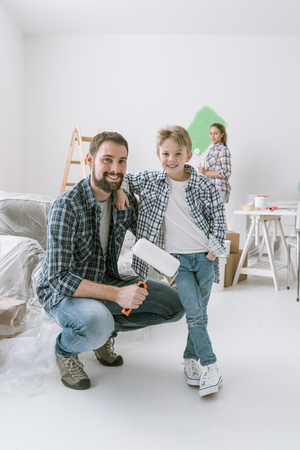 Home makeover, decoration and painting: a father is posing with his son and holding a paint roller, his wife is painting walls on the background