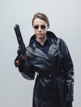 Cool female spy agent in black leather coat, she is holding a gun and posing Standard-Bild
