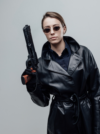 Cool female spy agent in black leather coat, she is holding a gun and posing Stockfoto