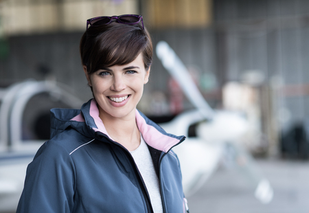 Smiling confident woman posing with her airplane in the hangar before departure, aviation and light aircrafts concept Stock Photo