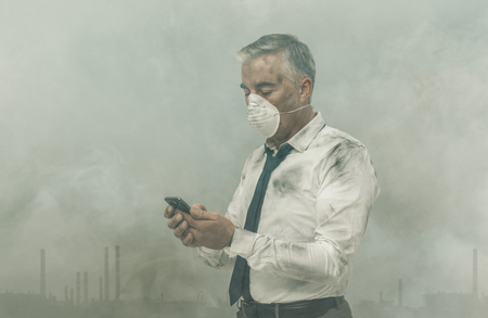 Corporate business executive with protective mask and polluted air, he is using a smartphone Stockfoto