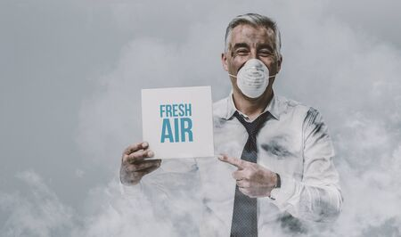Confident man wearing a pollution mask and holding a fresh air sign 스톡 콘텐츠