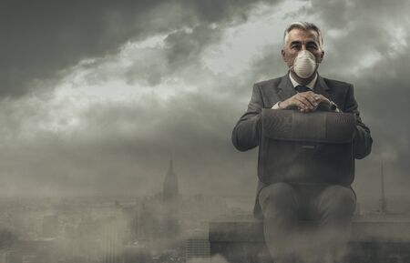 Businessman sitting on a rooftop in a polluted city, he is pensive and looking away: business and pollution concept