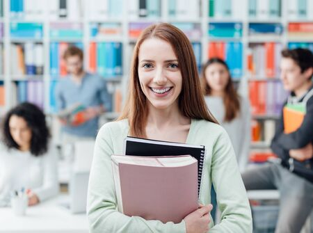 Smiling female university student posing with notebooks and students on the background, learning and education concept