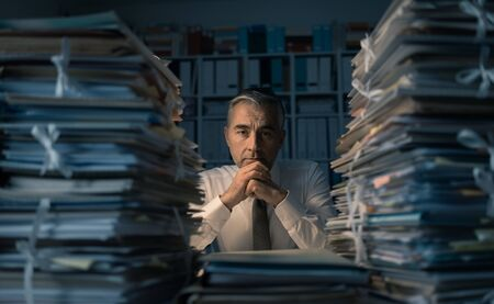 Stressed exhausted business executive working in the office late at night with piles of paperwork, he is overloaded with work: management and deadlines concept