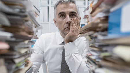 Frustrated overwhelmed executive working in the office and overloaded with paperwork, he is leaning on his arm and feeling depressed