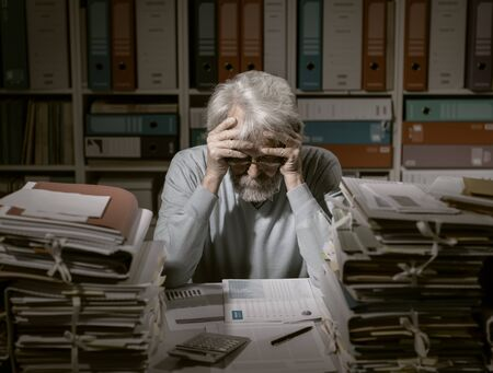 Overloaded stressed senior office worker with head in hands, his desktop is filled with paperwork and files Banque d'images