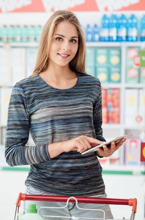 Smiling young woman shopping at the supermarket, she is checking products and offers on her digital tablet