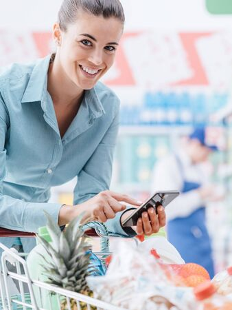 Smiling young woman doing grocery shopping at the supermarket, she is leaning on the shopping cart and connecting with her phone, apps and retail concept Stock Photo