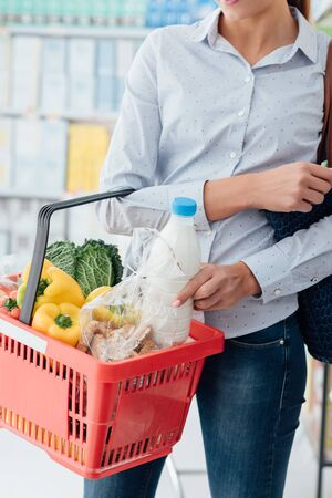 Woman doing grocery shopping at the supermarket, she is putting a bottle of milk into a shopping basket Stockfoto