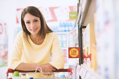 Happy woman doing grocery shopping at the supermarket, she is leaning on a full shopping cart, lifestyle and retail concept