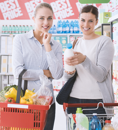 Friends doing grocery shopping together at the supermarket, they are smiling at camera and posing