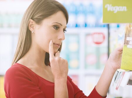 Young woman choosing products on the supermarket shelves and reading labels, she is thinking with hand on chin Stock Photo