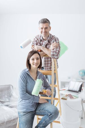 Happy couple renovating their house and painting a room, they are leaning on a ladder and posing with paint rollers