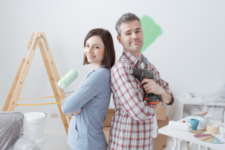 Smiling loving couple doing home renovations, the woman is holding a paint roller and the man is using a drill Stok Fotoğraf