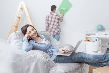 Happy couple doing home renovations, the man is painting the room and the woman is relaxing on the armchair and connecting with a laptop