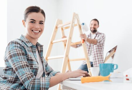 Young smiling couple renovating and remodeling their new apartment, the man is painting the walls with a roller and the woman is connecting with a laptop