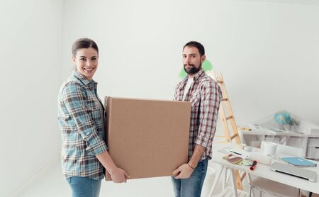 Young smiling couple moving into a new house, they are carrying full cardboard boxes Stok Fotoğraf