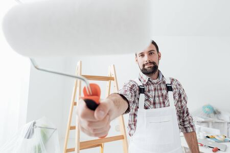 Smiling professional painter working and painting, paint roller on the foreground, home renovation and decoration concept