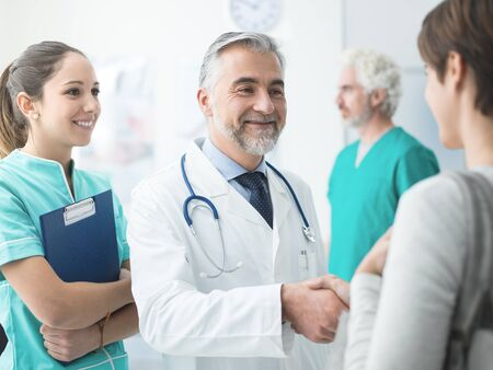 Smiling confident doctor shaking patients hand at the hospital and medical team